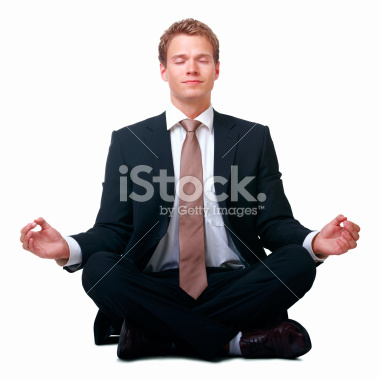 Man meditating in a suit.
