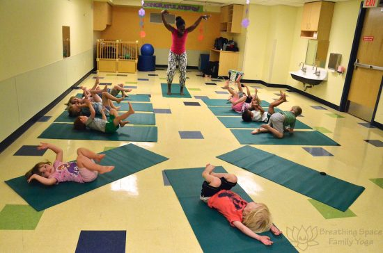 preschool yoga at a daycare, students on the floor with legs up