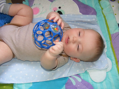 baby playing with hollow ball with circle holes