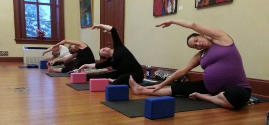 prenatal moms stretch in yoga class